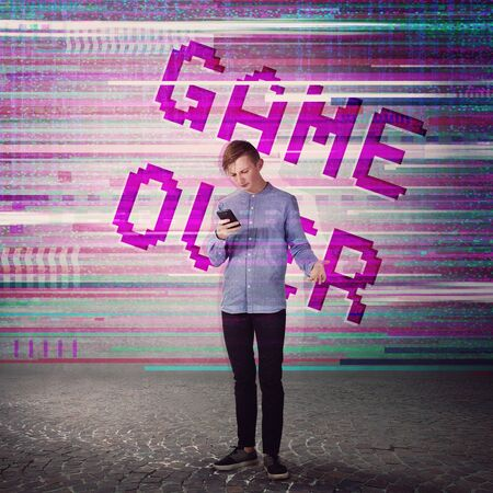 Displeased adolescent boy using mobile phone has lots of software  bugs and errors. Gamer angry of glitch on the screen and text game over. Addicted guy playing video games, lost in the virtual world.