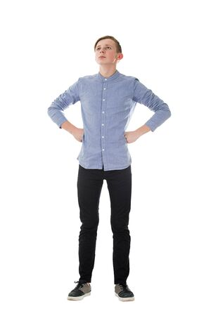 Full length portrait casual boy teenager posing hands on hips showing chest and power like a superhero isolated over white background. People confidence expression, strength and motivation concept.
