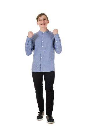 Full length portrait of a cheerful teenage boy raising his hands up, holding fists, like a winner celebrating success and victory isolated on white background. Banco de Imagens