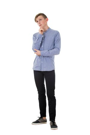 Full length portrait upset and thoughtful teen guy, hand to chin, has no ideas for the feature being in despair. Adolescent negative emotions and thinking concept isolated over white background. Imagens
