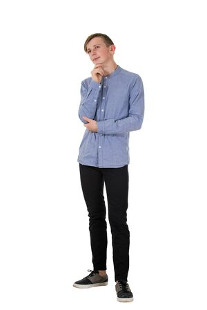 Full length of handsome cheerful boy teenager wearing casual jeans and shirt, hand to chin, positive thinking looking away isolated over white background with copy space.