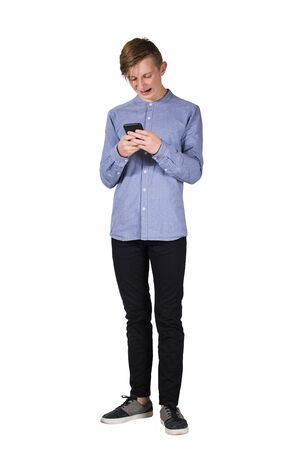 Full length portrait of teen boy using his smartphone being stressed and desperate after bullying on social media isolated over white background. Cyberbullying concept as guy feel offended online.