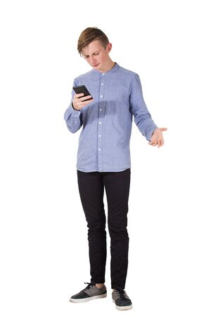 Full length portrait of angry adolescent boy using his mobile phone being frustrated and desperate isolated over white background. Teenager in disagreement with news received on smartphone.