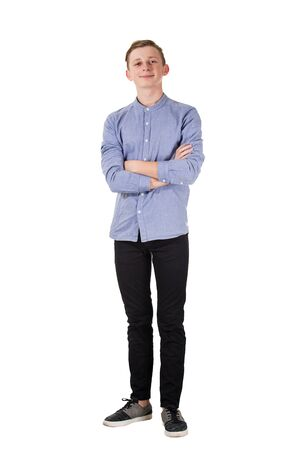 Full length portrait of casual, confident teenage boy posing with arms crossed isolated over white background with copy space. Happy facial expression looking to camera. Banco de Imagens