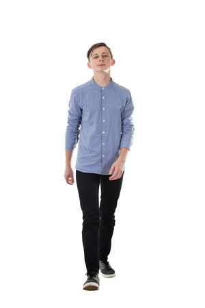 Full length portrait of joyous casual teenage boy walking relaxed towards camera isolated over white background. Confident facial expression, motion shot making a step.