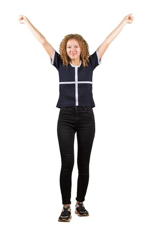 Success positive emotions, freedom concept. Full length portrait of happy teen girl, curly hair, lifting hands up looking to camera isolated on white background.