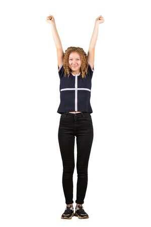 Full length portrait of a cheerful adolescent girl, curly hair, raising hands up. Celebrate success like a winner, freedom concept isolated on white background. Banco de Imagens