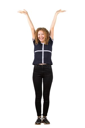 Full length portrait of a joyful adolescent girl, curly hair, raising hands up. Celebrate success like a winner, freedom concept isolated on white background.