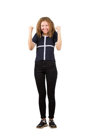 Full length portrait of excited teen girl, curly hair, positive smiling holding fists raised up celebrating success and luck isolated on white background.