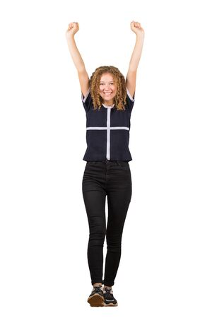 Full length portrait of a cheerful adolescent girl, curly hair, raising hands up as making a step forward. Celebrate success like a winner, freedom concept isolated on white background.
