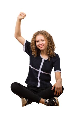 Full length portrait of carefree teen girl sitting on the floor, curly hair, raising one hand up looking positive to camera isolated on white background.