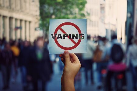 Human hand holding a protest banner stop vaping message over a crowded street background. Banning flavored vaping products to discourage people from smoking electronic cigarettes. Health risk concept. Banco de Imagens