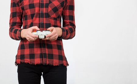 Close up of teenage boy hands playing video games holding a joystick console isolated over white background with copy space. Focused guy having fun in the virtual world. Banco de Imagens