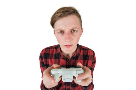 Close up portrait of addicted teenage boy has problems due to video games addiction, looking confused to camera, holding joystick console don't stop playing isolated over white.