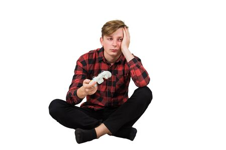 Bored adolescent boy seated on the floor playing video games isolated over white background. Sleepy boy holding joystick console, being in a bad mood after losing in the virtual world.
