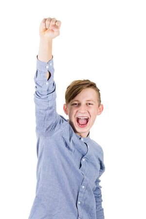 Excited boy teenager raising one hand up, holding fist and screaming as achieving success. Positive emotions celebrating victory as a winner isolated over white background.