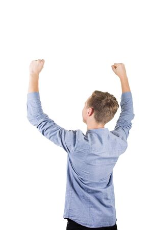 Rear view of successful student boy teenager raising hands up isolated over white background. Adolescent guy celebrate victory as a winner.