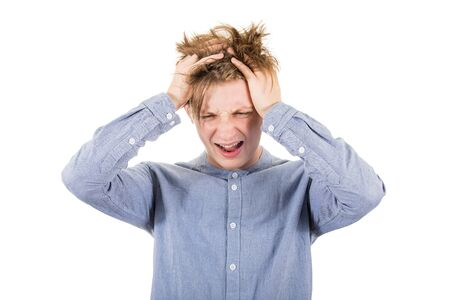 Frustrated teenage boy messing up and pulling his hair, hands to head, looking down shouting and screaming, isolated over white background with copy space. Stressed adolescent, failure concept. Stock Photo