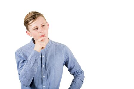 Smart teenage boy thinking, keeps hand under chin looking aside isolated over white background.
