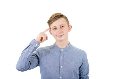 Portrait smart teenage boy pointing forefinger to his head showing where genius ideas came from, isolated over white background.