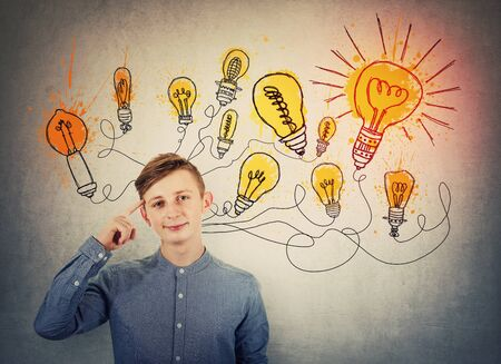 Confident teenage boy pointing forefinger to head showing where genius ideas come from, and shining light bulbs sketches like different thoughts. Genius creativity concept, planning way to success.
