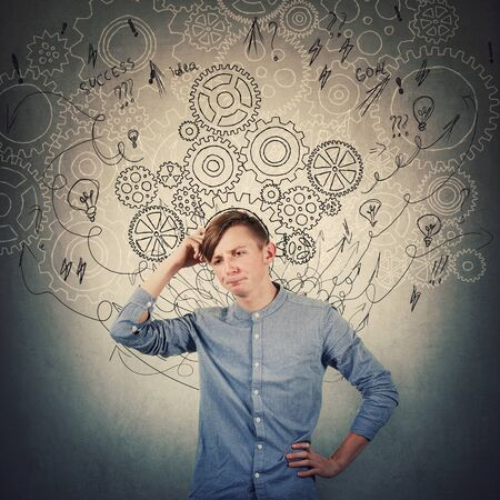 Pensive teenage boy scratching his head looking confused has questions. Perplexed guy thinking of new ideas as gear cogwheels, arrows and mess sketch as thoughts around head. Find solution to problem. Stock Photo