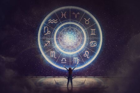 Woman raising hands looking at the night sky. Astrological wheel projection, choose a zodiac sign. Trust horoscope future predictions, consulting stars. Power of universe, astrology esoteric concept. Stockfoto