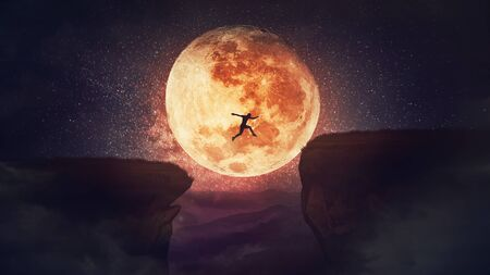 Surreal scene, self overcome concept, as determined man jump over a chasm obstacle. Way to win and success over starry night with full moon background. Motivation for achieving goals.