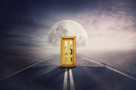 Scary scene with spirit silhouettes coming from another world, parallel universe, try to open a door in the middle of a road. Spooky hands pushing behind doorway, try to enter. Mystic way to full moon Stock Photo