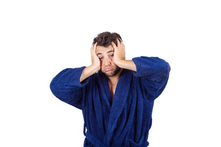 Portrait of tardy young man wears blue bathrobe holding hands to head, unable to wake up in time to get to work, isolated on white background. Stock Photo