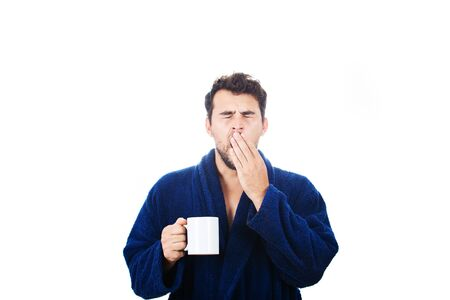 Portrait of tardy young man wears blue bathrobe holding cup of coffe and yawning unable to wake up in time to get to work, isolated on white background.