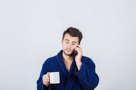 Portrait of sleepy young man messy hair, wears blue bathrobe, drinking coffee from his cup and speking on phone isolated on white background.