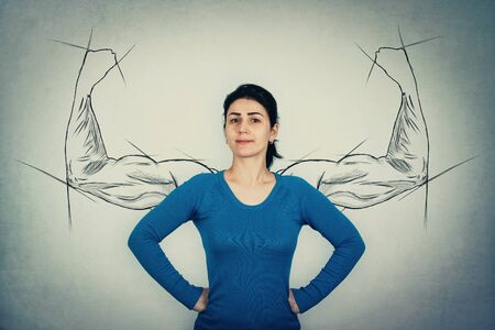 Brave woman, hands on hips, facing fears like a powerful hero as muscular arms sketches on the wall showing her inner strength. Strong girl showing big biceps. Self defense and confidence concept. Imagens