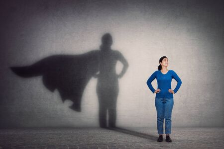 Brave woman keeps arms on hips, smiling confident, casting a superhero with cape shadow on the wall. Ambition and business success concept. Leadership hero power, motivation and inner strength symbol. Stockfoto