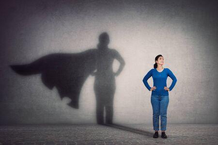 La donna coraggiosa tiene le braccia sui fianchi, sorride sicura, lancia un supereroe con l'ombra del mantello sul muro. Ambizione e concetto di successo aziendale. Potere dell'eroe di leadership, motivazione e simbolo di forza interiore.