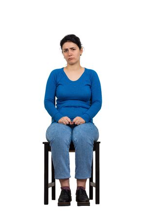Sad and disappointed woman sitting on a chair looking indisposed to camera, full length isolated over white background. Upset casual girl having anxiety, distress depression feeling, seated alone.