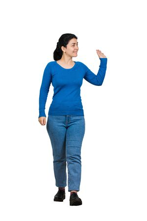 Full length portrait of carefree friendly young woman, smiling broadly while waving palm raised up, greeting friend, say hello gesture. Casual girl wearing blue jeans and sweater isolated over white.