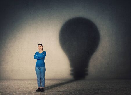 Confident woman, keeps arms crossed, casting a lightbulb shape shadow on the wall. Ambition and business idea concept. Genius innovation, motivation and inner power symbol.