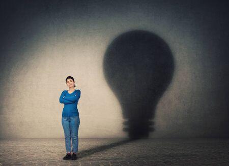 Donna sicura di sé, tiene le braccia incrociate, proiettando un'ombra a forma di lampadina sul muro. Ambizione e concetto di idea imprenditoriale. Innovazione geniale, motivazione e simbolo del potere interiore.