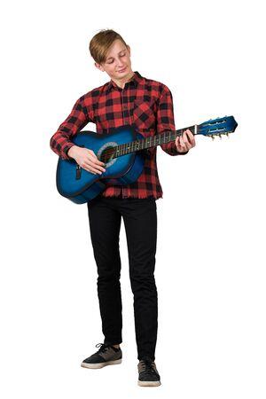 Ganzaufnahme des stolzen Jungenjugendlichen, der auf der akustischen Gitarre spielt, die über weißem Hintergrund lokalisiert wird. Musikunterricht für Schüler. Ein talentierter Kerl möchte ein berühmter Musiker werden. Standard-Bild