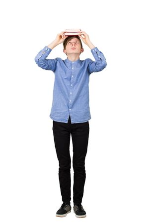 Full length of student boy looking up confused, holding books over head. Knowledge and educational concept, teen guy reader has questions isolated over white background with copy space. Фото со стока