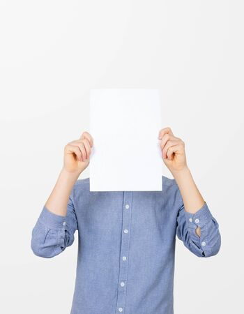 Teenage boy holding blank sheet of paper infront of his face. Man covering face with blank sheet of paper for hiding his identity. Фото со стока