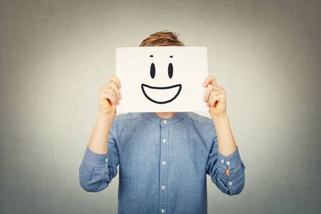 Teenage guy covering face using a white paper sheet with smiling emoticon sketch, like fake mask for hiding identity and real emotion from society. Introvert male anonymity concept over grey wall. Фото со стока