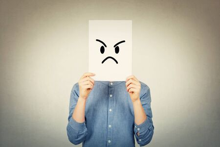Teen boy covering face using a white paper sheet with angry sad emoticon sketch, like fake mask for hiding the real emotion from society. Introvert guy anonymity concept over grey wall.