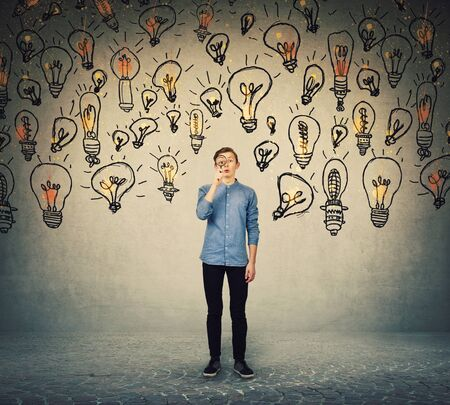 Ingenioso adolescente que busca ideas brillantes mientras mira con curiosidad a través de la lupa. El estudiante intenta encontrar soluciones a todos los problemas, ya que lo rodean muchas bombillas.