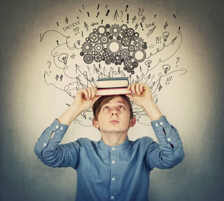 Student boy looks up curious as holds two books on his head, feeling overwhelmed and exhausted of constant learning. Cogwheel brain, arrows and curves sketches as thoughts. Mental development concept.