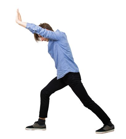 Determined teenage guy making effort as pushing an heavy invisible object isolated on white background. Confident boy, difficult task concept, convinced in his powers, finding solutions to problems.
