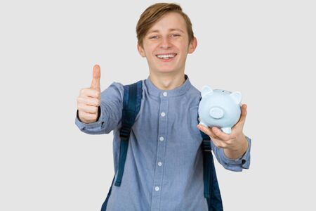 Teenager boy holding piggy bank  with thumb up signs over white background. Financial education savings concept.