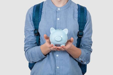 Teenager boy holding piggy bank over white background. Financial education savings concept Stok Fotoğraf