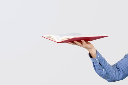 Teenager hand holding a  open book isolated on a white background.